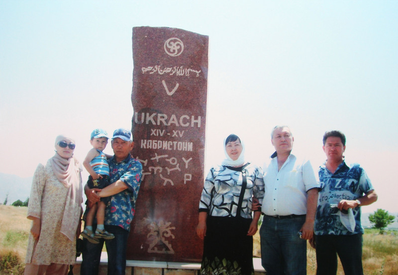 Рядом с надгробным камнем стоят потомки Өкіреш Шала из Казахстана. Слева направо: Арайлым Рахым, Камал Абдрахман, на руках у него Асыл-Гали Камалұлы, Карлыга Абдрахманова, Максут Калажанов, Толыбек Сулейменов;